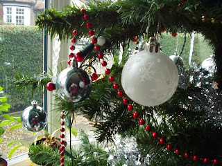 A colour photo of the baubles on my christmas tree, with my bay window in the background.