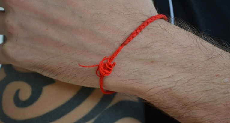 The ritual of wearing the amulet The Red Thread
