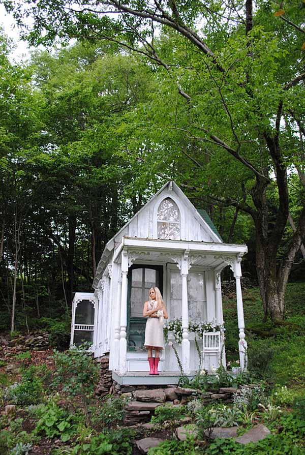 pequeña cabaña con glorieta en el jardín blanca