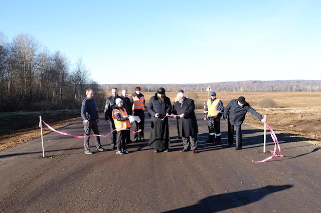 Новую дорогу на Гремячий ключ символически открывают игумен Савва и представители дорожных строителей.