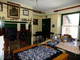 19th century or early 20th century living room, range fireplace, crowded with furniture, hanging washing airer, dark pictures on the walls, proggy rugs on the table.