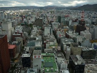 View of Sapporo city taken from 160m from the ground at the JR tower at Sapporo station. Some clouds and mountains in the background