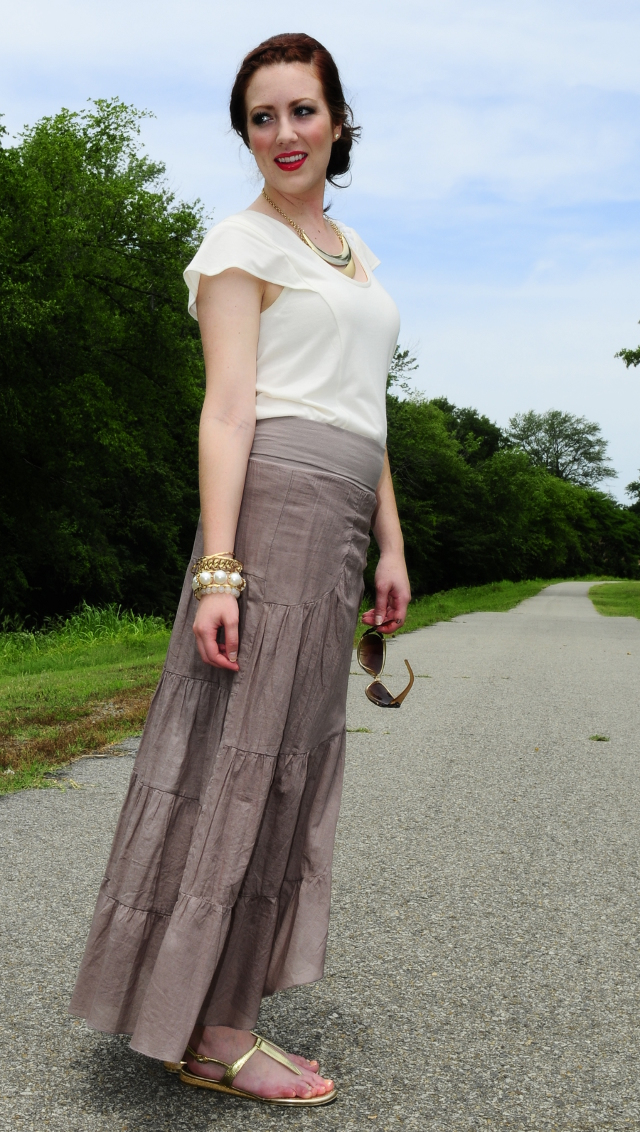 Tan tiered skirt, cream blouse, and gold accents