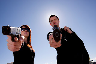 Photo of man and woman with guns.
