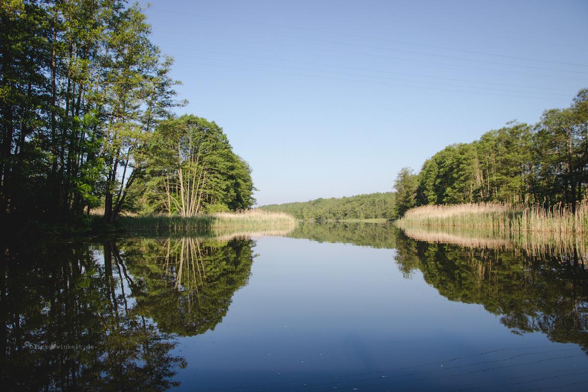 stiller Fluss mit klarem Himmel und Wasserspiegelung