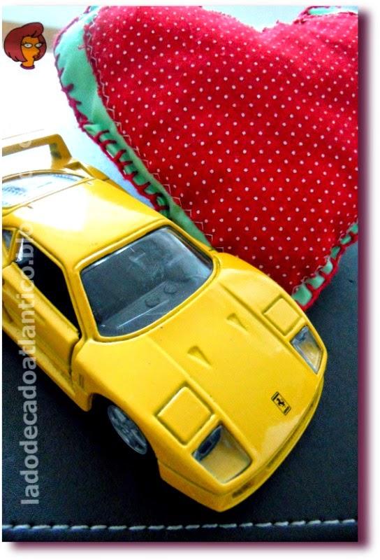 """Foto de um coração em tecido da """"Ação do Coração"""", Santos, e uma miniatura de Ferrari amarela de brinquedo"""
