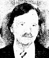 News clipoping photo, poor quality, of a middle-aged white man with a receeding hairline and a mustache, wearing a jacket and tie
