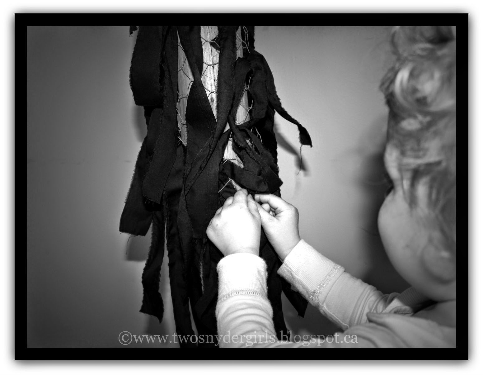A child placing black cloth on the cross
