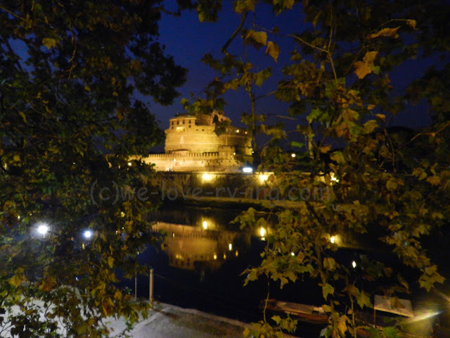A night scene with lights showing the castle across the Tiber River