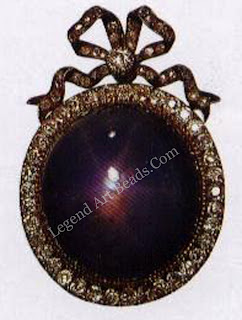 Above right, a star sapphire pendant set within a diamond border and surmounted by a bow knot.