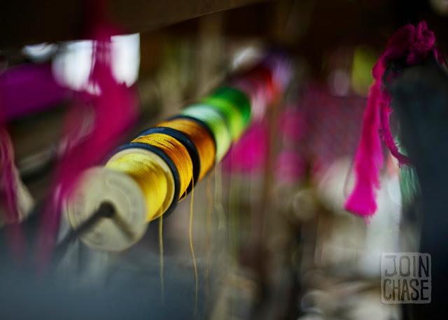 Colorful thread hanging above a wooden loom in Sagaing Division, Myanmar.