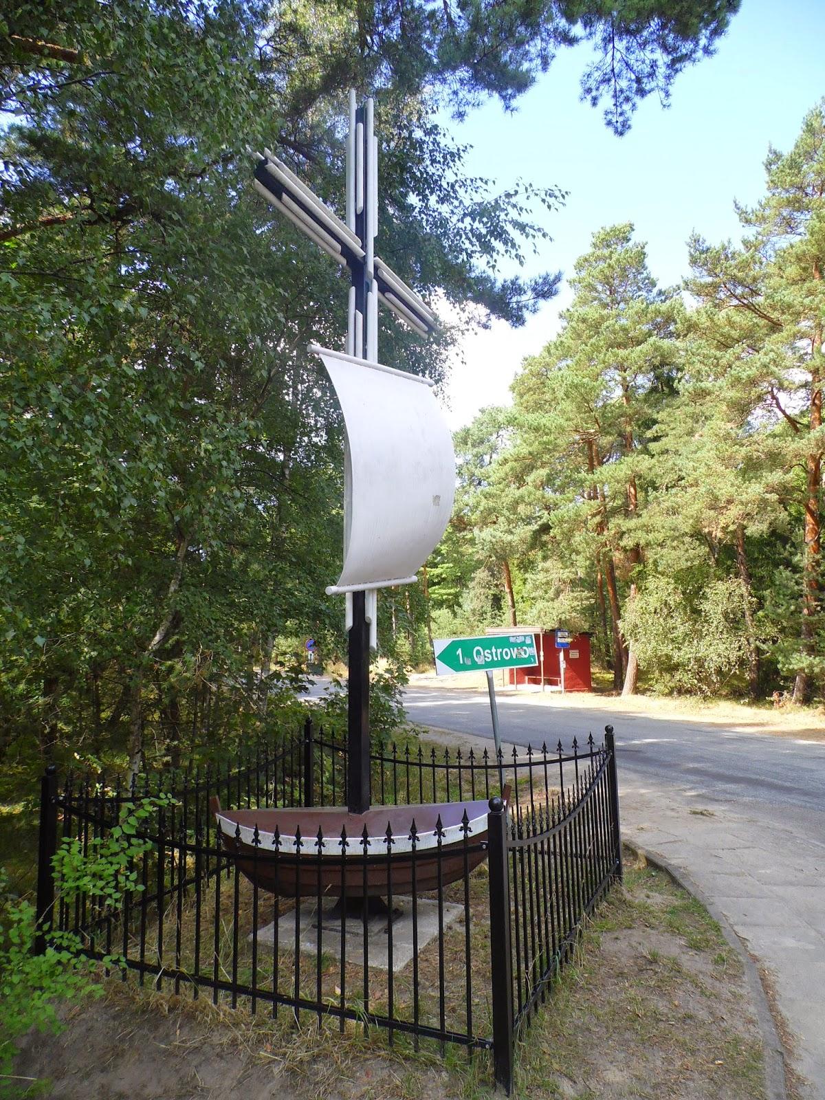 Krzyż, przystanek i drogowskaz przy zjeździe z głównej drogi do Ostrowa