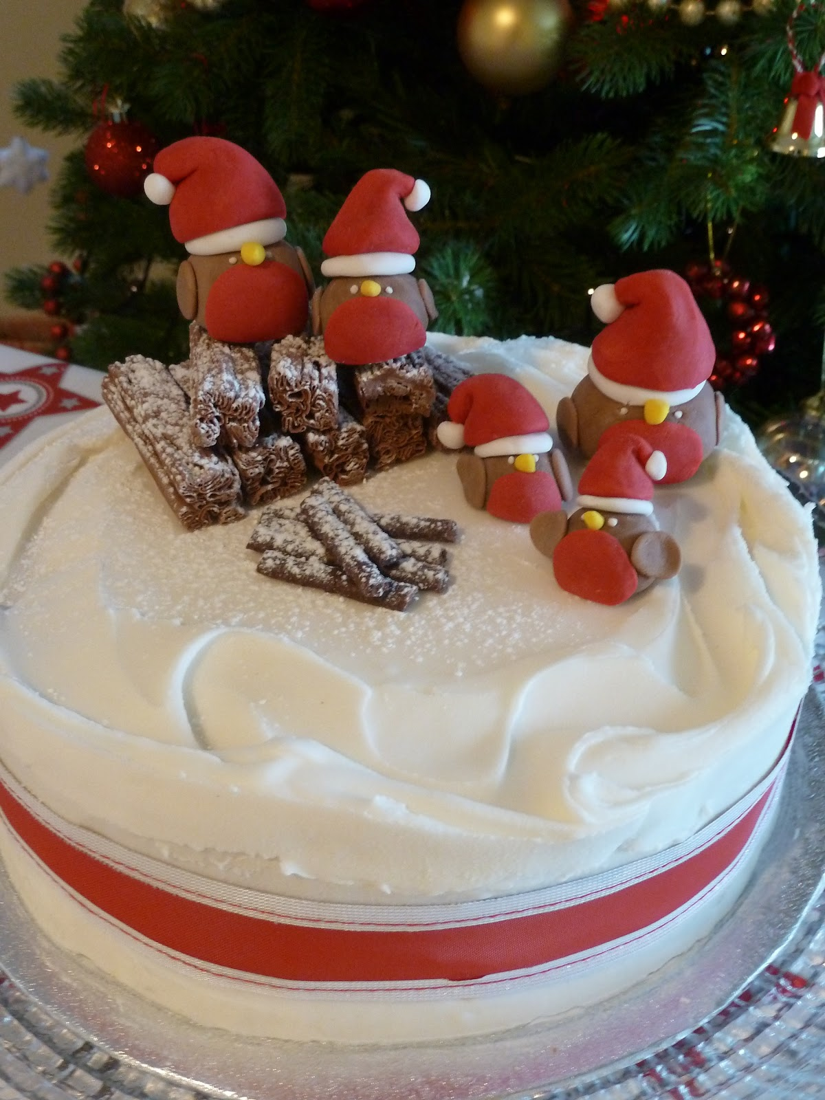 christmas cake decorated with swirled royal icing and sugar paste robins
