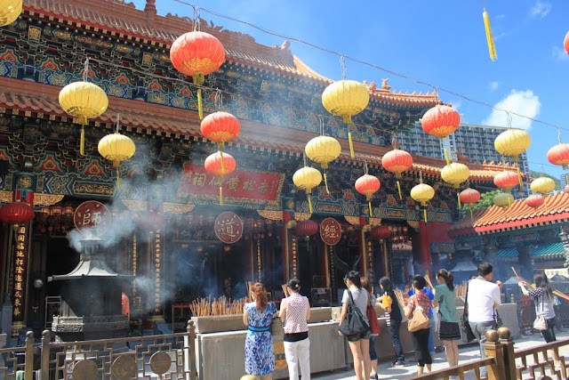 Visitors offer burning intense sticks in front of the God at Wong Tai Sin Temple in Kowloon, Hong Kong