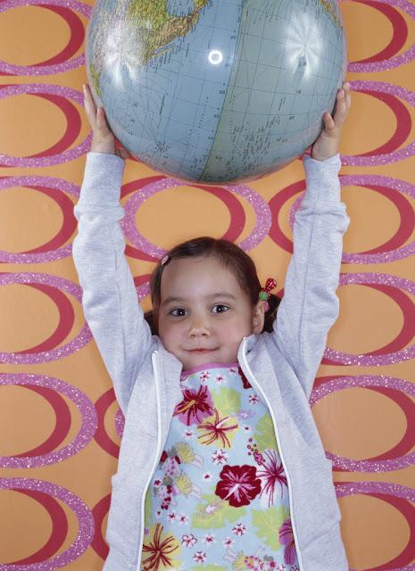 Una niña levantando con sus manos una bola del mundo.