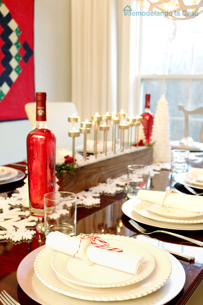 red bottles, candy cane napkin holders and candelabra on Christmas table