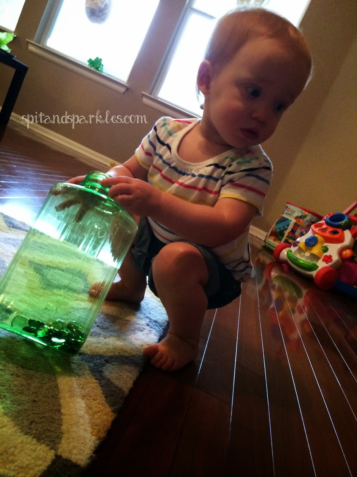Fill a large container with glass beads and teach baby how to dump out and fill up for a fine motor skills activity. #totschool #homeschool #earlylearning #StPatricksDay