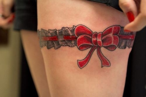 Red bow garter tattoo on upper leg Female tattoo