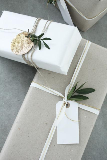 Paquete de regalo envuelto y decorado con rama de olivo