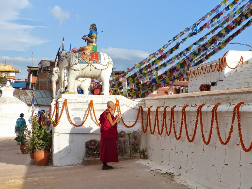 Tibetan monk praying at the Boudhanath stupa, Kathmandu, Nepal
