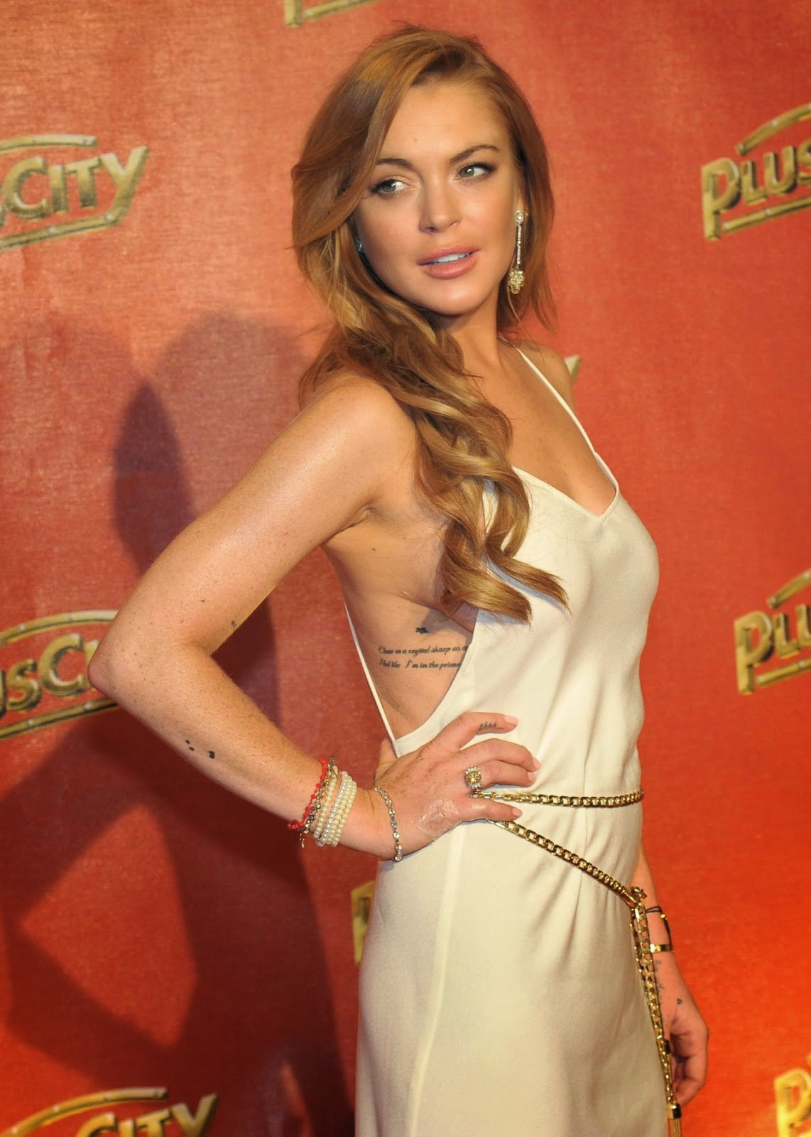 Lindsay Lohan goes braless in a slinky white gown at 'The White Party' in Austria