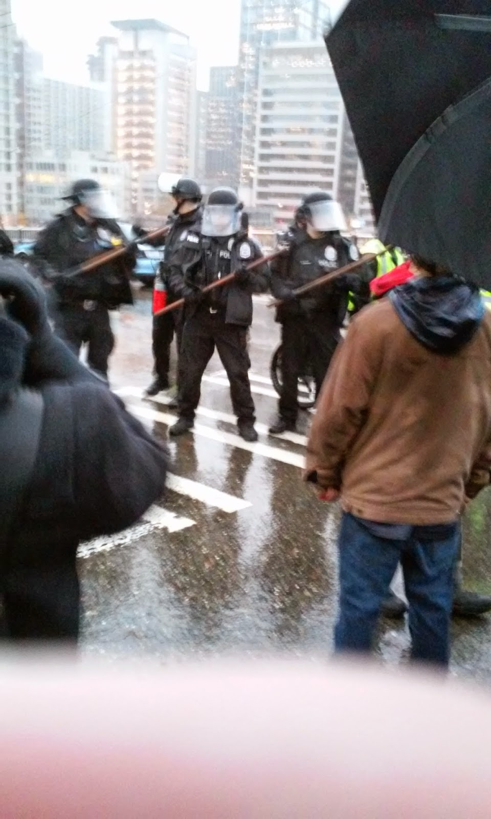 Photo of police line, with cops in riot gear holding clubs in front of them