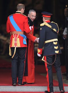 The Dean of Westminster John Hall (c.) shakes hands with Prince Harry and Prince William.