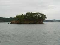Photo of matsushima pine island from boat on a cloudy day. Sort of a wedge shape