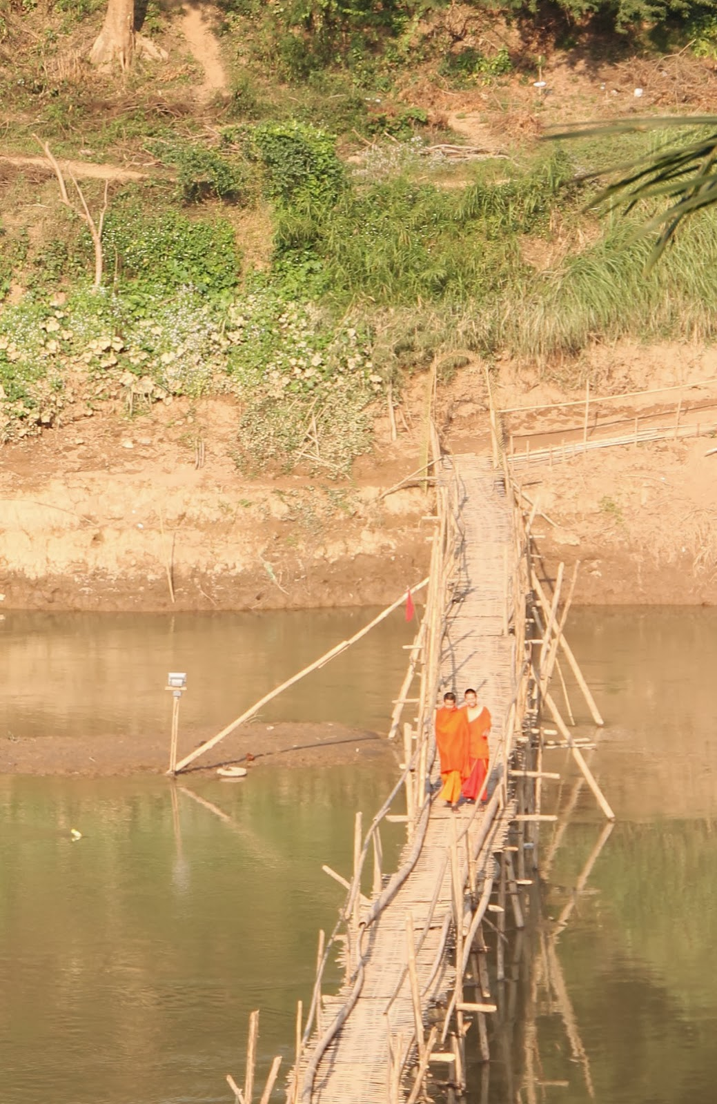 Monks crossing the Kahn River on a rickity bamboo bridge.