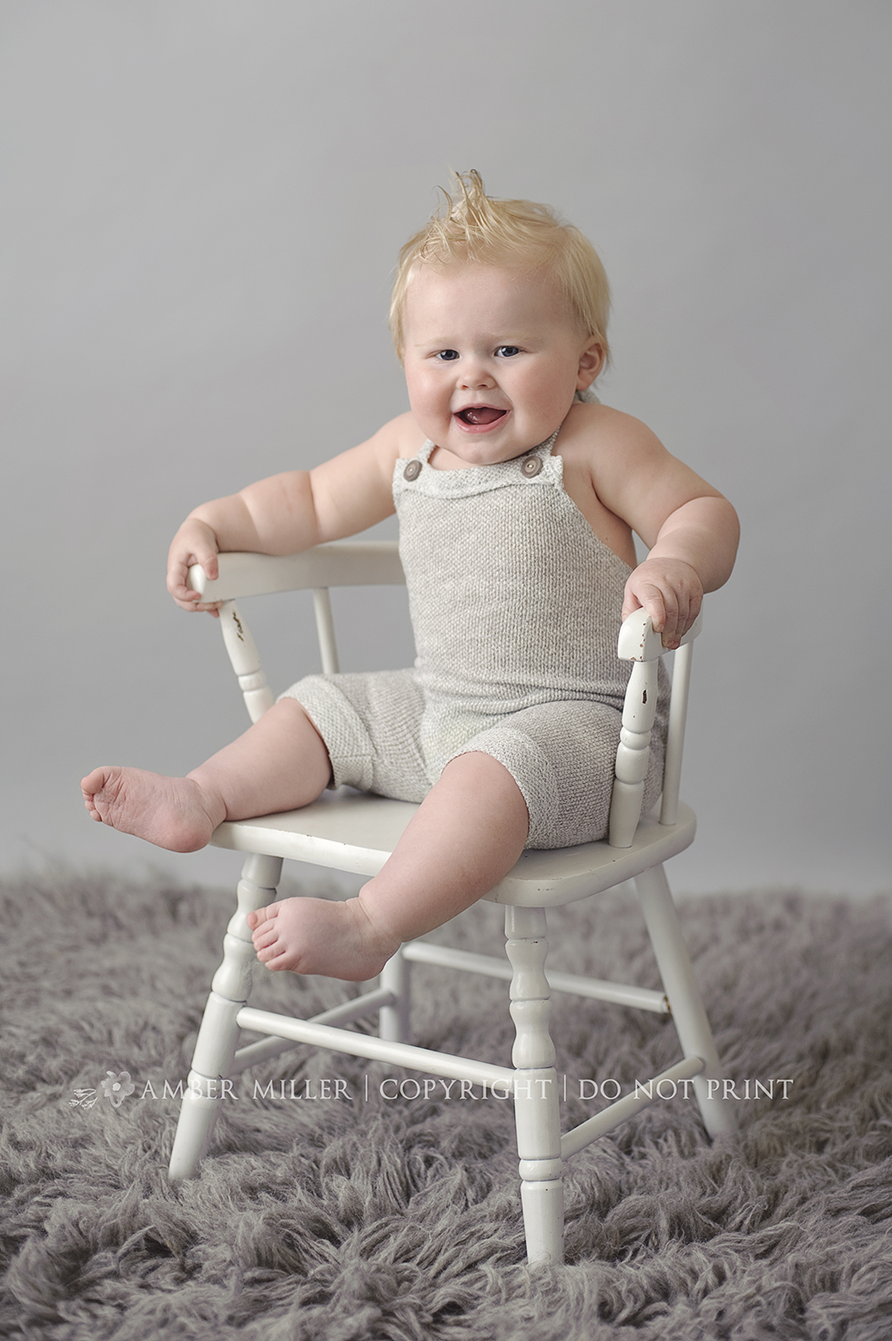 baby boy photographed on gray rug and background