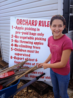 girl in front apple picking sign: simple living and eating