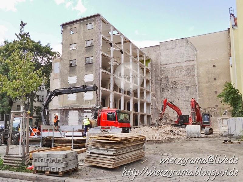Das Foto zeigt eine vergleichsweise kleline Baustelle in Berlin Kreuzberg auf der zwei Arbeiter sowie zwei Kraene und andere Arbeistfahrzeuge zu sehen ein Quergebaeude mit fehlernder Seitenwand