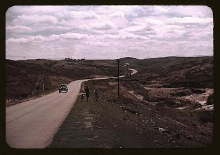 Foto antigua. Camino de terrizo. Un coche por él. Varias personas caminan por su borde.