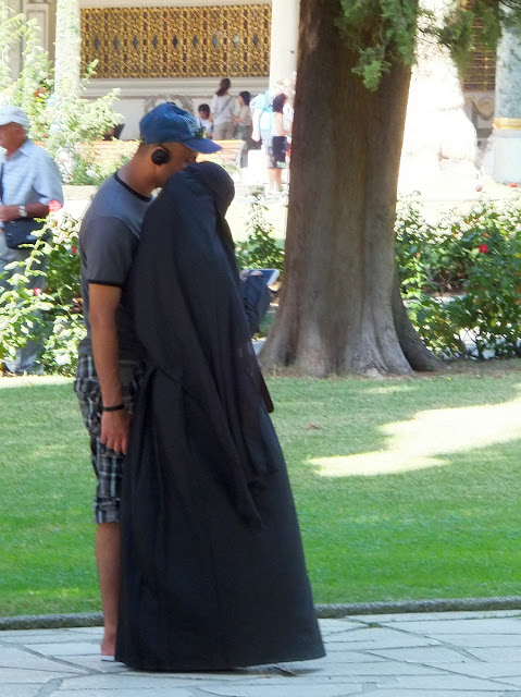 Парочка: парень в шортах с бейсболкой и девушка в чадре.