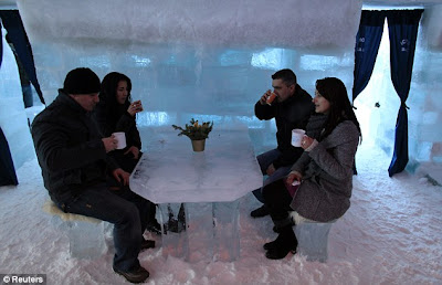 Wrap up warm!Tourists sit at a table serving warm drinks inside the Balea Lac Hotel of Ice in the Fagaras mountains