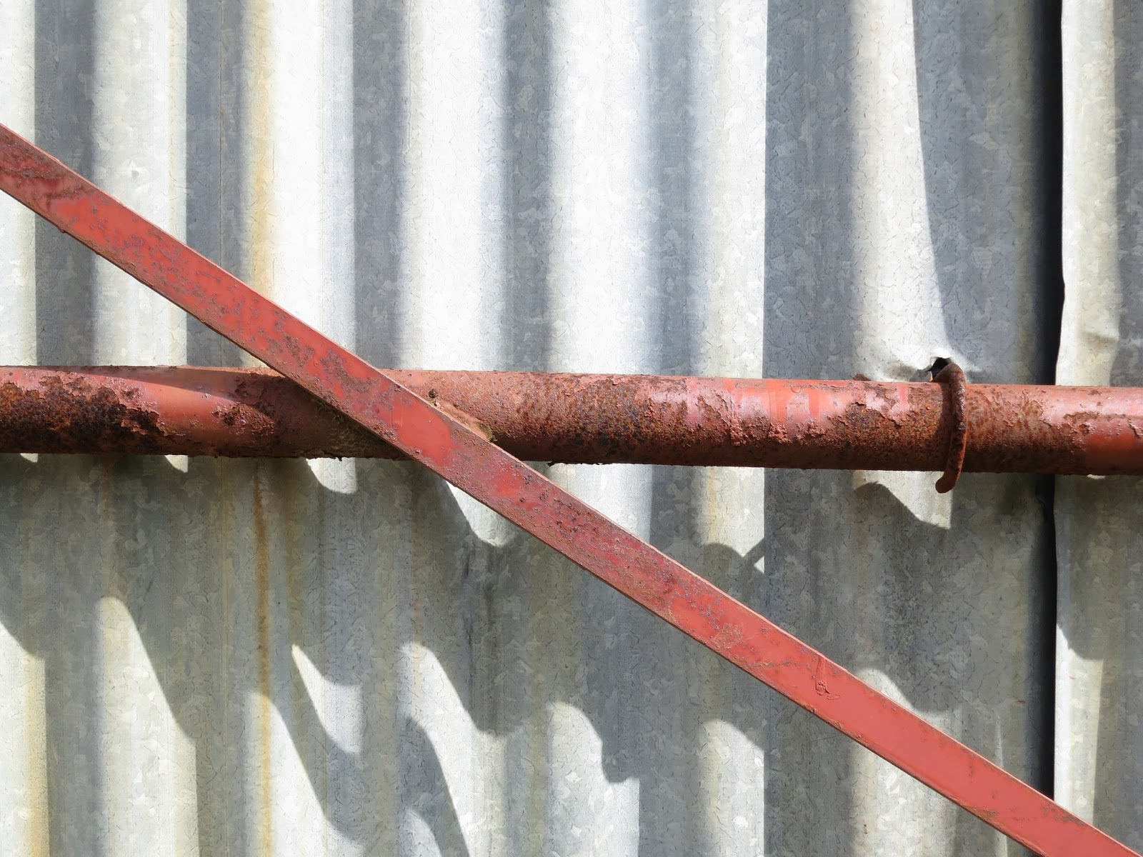 Corrugated iron wall of barn with rusty metal supports