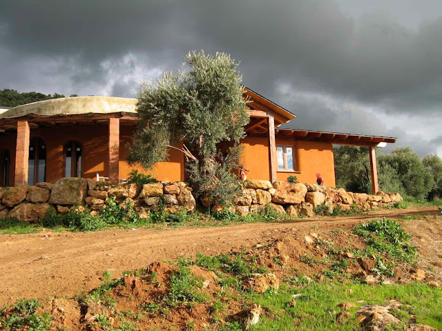 Внешний вид соломенного дома оштукатуренного красной глиной. Испания.