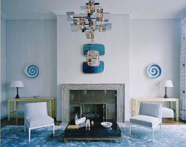 Alternative view of the living room with a fireplace, grey walls, a small mirror, two lavender chairs, a low coffee table and decorative plates as wall decor