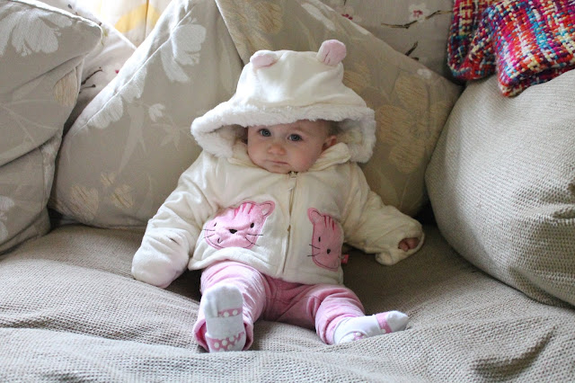baby wearing pink h&m trousers with white cat coat from tk maxx