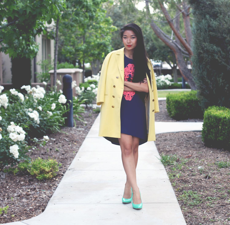 Honey & Silk wearing yellow Jill Stuart coat, Sugarlips filigree dress, and Cole Haan Chelsea Pumps