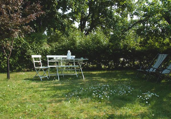 Vita trädgårdsmöbler framför en häck och stora träd i bakgrunden.