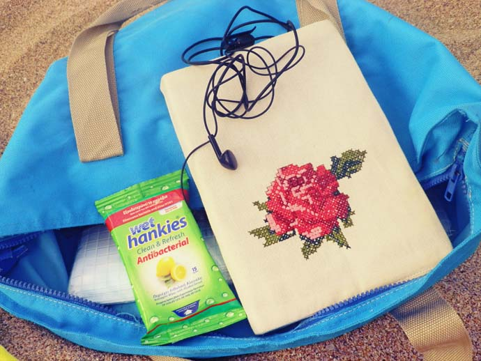 My blue beach bag, a book in a rose embroidered cover, headphones, wed wipes,