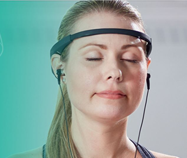 A young woman meditates, using the wearable technology Muse and her headphones to concentrate.