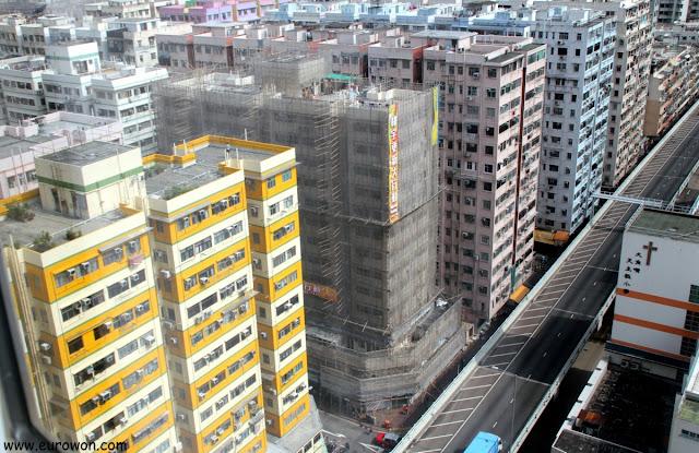 Edificio recubierto de andamios de bambú y una red protectora