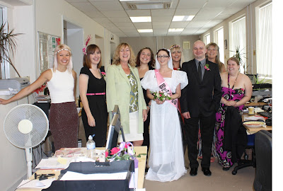 An office full of people dressed in wedding attire, with a bride and groom at the front