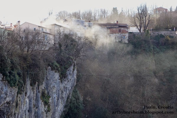 Winter chimney smoke floats above a natural stone wall and cave in Pazin Istria Croatia