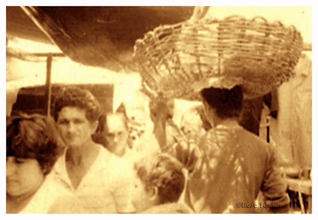 Em primeiro plano são vistos, centralizado na parte inferior da imagem, de costas, cabeça de um menino voltada para o lado esquerdo, à direita do menino, homem jovem com grande balaio vazio sobre a cabeça e no lado esquerdo, em fila indiana, de frente, parte do rosto de uma mulher de cabelos curtos e lisos olhando para baixo, uma mulher de cabelos curtos e crespos e um homem calvo, estão sérios. Ao Fundo desfocados, estruturas das barracas em madeira, lonas, roupas penduradas à direita, e mais pessoas.