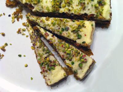 Immagine della torta di carote e pistacchi ricoperta di glassa al cioccolato bianco e limoncello e granella di pistacchi