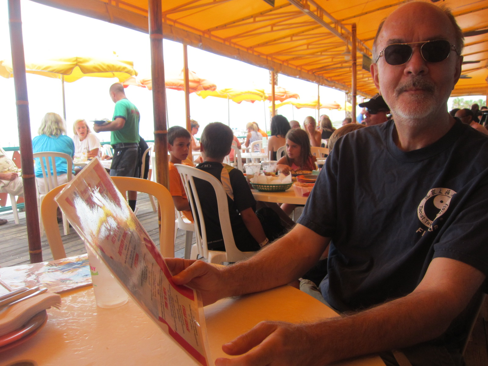 Fred, holding his menu up, three of the urchins are visible in the background.
