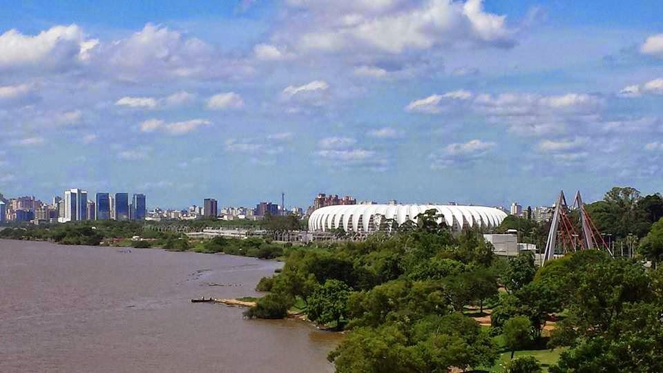 O cartão postal da cidade de Porto Alegre retrata uma vista panorâmica, à esquerda, o rio Guaíba com a orla bem arborizada e à direita, em destaque, o gigantesco estádio Beira-Rio de arquitetura circular, arrojada e branca, que lembra a carapaça de um ouriço-do-mar sem espinhos. Ao fundo, vista parcial da cidade formada por prédios altos. No céu azul, algumas nuvens brancas.